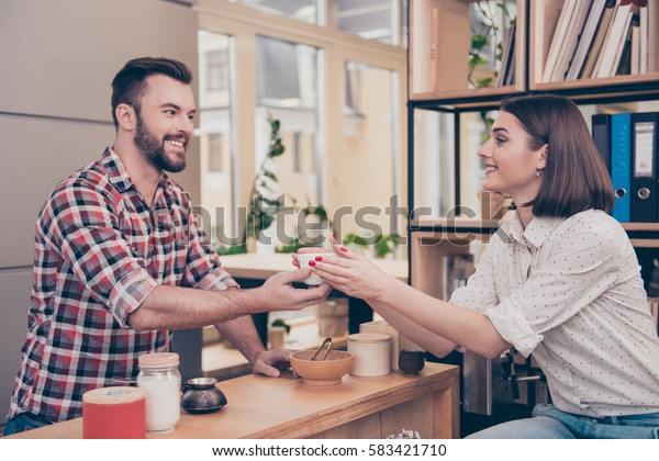 Smiling handsome male bartender giving cup of coffee to client