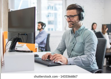 Smiling handsome male customer support phone operator with headset working in call centre. Group of sales agent working in office.