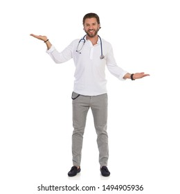 Smiling handsome male doctor holds hands raised and compares something. Front view. Full length studio shot isolated on white.