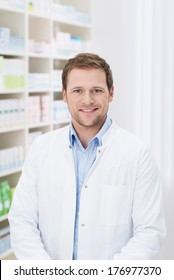 Smiling handsome male pharmacist standing in the pharmacy in his white coat