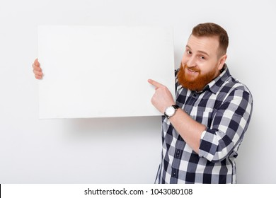 smiling handsome man with beard holding big white card. empty blank board