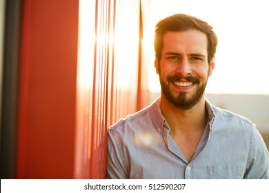 smiling handsome man with beard looking to camera with sun behind
