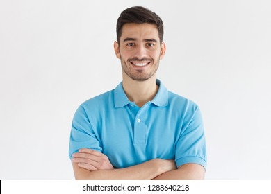 Smiling handsome man in blue polo shirt standing with crossed arms isolated on gray background