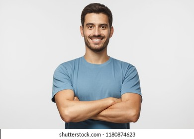 Smiling handsome man in blue t-shirt standing with crossed arms isolated on gray background