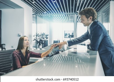 Smiling handsome man in formal suit is leaning on table top and giving his debit card to charming caucasian woman working on reception to pay his bills, modern bright interior of office or hotel