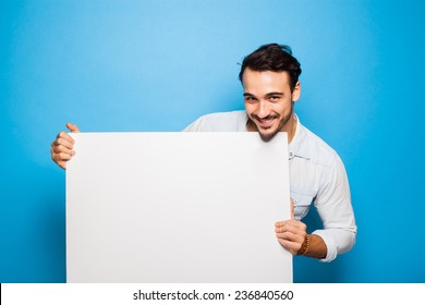 smiling handsome man looking into camera and holding a blank panel on blue background