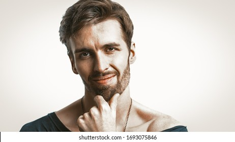 Smiling Handsome Man Looks At Camera And Touching The Chin With His Hand, Studio Portrait Close Up Of Caucasian Pensive Man, Isolated On White Background, Copy Space Are At Right Side