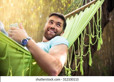 Smiling handsome man lying on hammok with smartphone outdoors