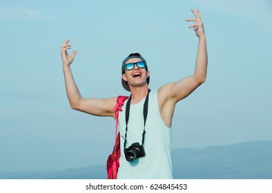 Smiling handsome man, photographer with camera, or traveler, with hands gesture raised to blue sky in stylish, fashionable sunglasses and cap on sunny summer day. Photography and hobby