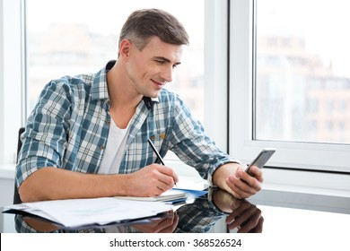 Smiling handsome man in plaid shirt writing and using mobile phone at the table