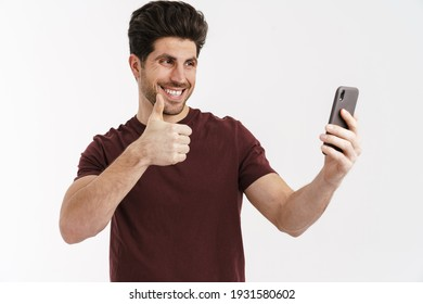 Smiling handsome man showing thumb up while taking selfie on cellphone isolated over white background