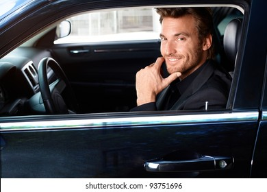 Smiling handsome man sitting in limousine.?