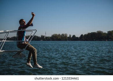 Smiling handsome man taking selfie while sitting on the river boat. Beautiful sunny day
