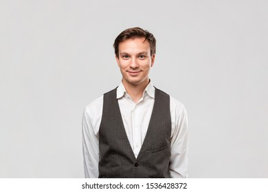 Smiling handsome man in a white shirt and grey vest looking at the camera standing isolated over grey background.