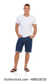 Smiling handsome man in white shirt, jeans shorts and black sandals standing with hands in pockets and looking at camera. Full length studio shot isolated on white.
