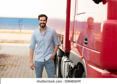 smiling handsome masculine driver stranding next to his red truck outside