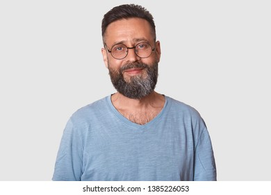 Smiling handsome middle aged man posing against white background, looks cheerful. Black haired attractive model with beard wearing grey t shirt and glasses, has calm and pleasant facial expression.