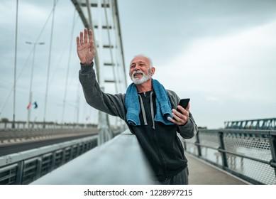 Smiling  handsome older runner greeting his running friends.