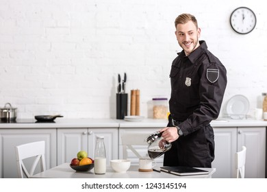 smiling handsome policeman pouring filtered coffee from glass pot at kitchen