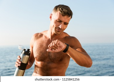 Smiling handsome shirtless sportsman holding water bottle while standing at the beach and checking smartwatch