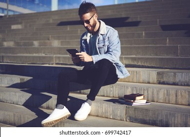 Smiling handsome trendy student in eyeglasses reading news and browsing useful information for coursework project on digital tablet connected to wireless internet while sitting on stairs outdoors