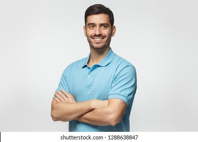 Smiling handsome young man in blue polo shirt standing with crossed arms, isolated on grey background
