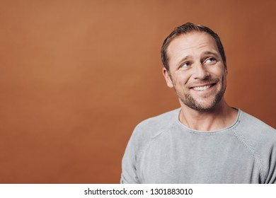 Smiling handsome young man in grey shirt looking away at right corner in bust front portrait with copy space against brown background