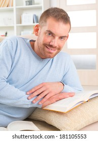 Smiling handsome young man reading storybooks on couch at home