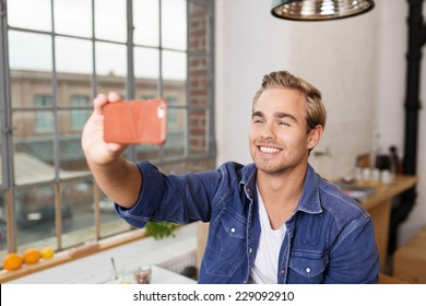 Smiling Handsome Young Man Taking Self Picture Using Mobile Phone Inside the House.