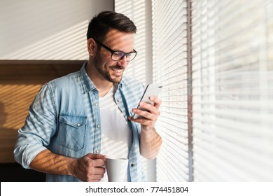 Smiling handsome young man using phone by the window