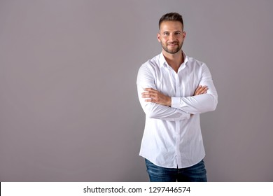 A smiling handsome young man in a white shirt standing in front of a grey background in the studio.