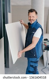 Smiling handyman or builder holding a large sheet of chip board for interior wall cladding looking at camera with a friendly smile
