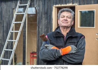 Smiling handyman with paintbrush outside a shed