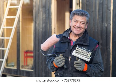 Smiling handyman with paintbrush and roller outside a shed