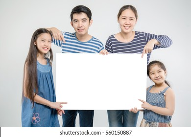 Smiling happy Asian family with big white poster on isolated background.