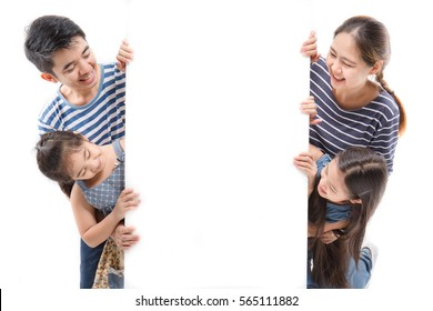 Smiling happy Asian family with big white poster on isolated background