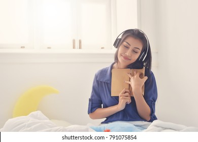 Smiling happy asian girl reading book and listening in wireless headphones, relaxing in bed at home , relaxation time concept