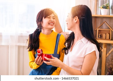 Smiling happy Asian teenage daughter and Asian middle-aged mother hugging together in indoor living room at home. Mum is holding a present gift.