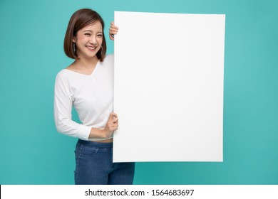 Smiling happy Asian woman holding and standing behind big white poster isolated on light green background