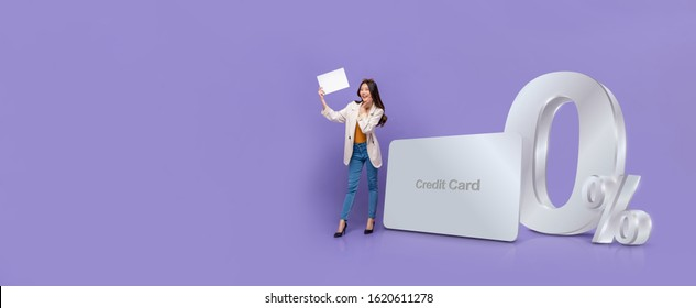 Smiling happy Asian woman holding white paper standing next to credit card with 0% interest installment payment promotion against purple banner background