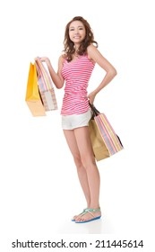 Smiling happy Asian woman shopping and holding bags, full length portrait isolated on white background.