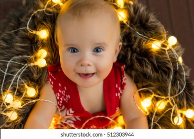 smiling happy baby in christmas lights and traditional holiday colors clothes laying in fur on wooden background and watching to the camera