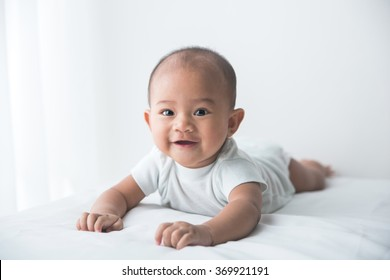 smiling happy baby tummy time on bed