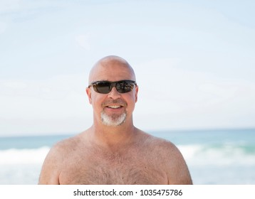 Smiling Happy Bald Man Wearing Sunglasses on the Beach in Mexico