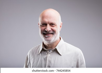 smiling happy bald old man portrait on a neutral gray background