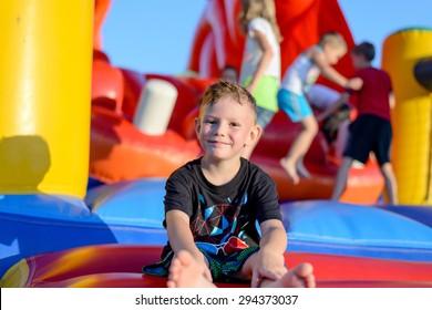 Smiling happy barefoot little boy sitting on a colorful inflatable plastic jumping castle at a fairground or kids playground