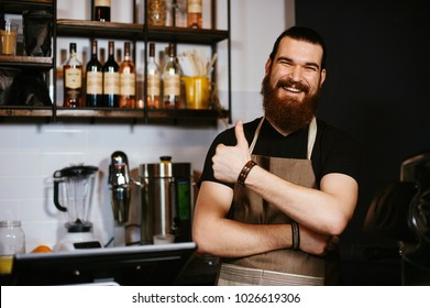 Smiling happy bearded hipster barista showing thumbs up gesture standing in restaurant.