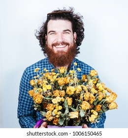 Smiling happy bearded man with bunch of dry yellow roses on white background. Woman's day. Curly hair. Love peace and flowers. Man with flowers looking at camera.