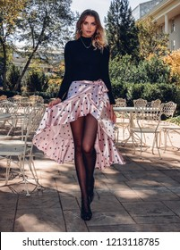 Smiling happy beautiful blonde fashionable young woman wearing a trendy outfit skirt sweater tights heels walking in city park. Street style. Flirty cute fashionable woman walking in the city outdoors