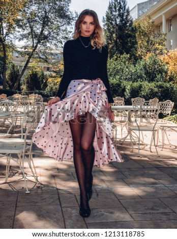 6bc2316026 Smiling happy beautiful blonde fashionable young woman wearing a trendy outfit  skirt sweater tights heels walking
